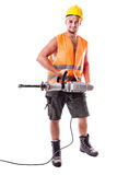 Road Worker holding a Jackhammer. A young road worker wearing a hardhat and a visibility vest holding a jackhammer isolated over white background Royalty Free Stock Images