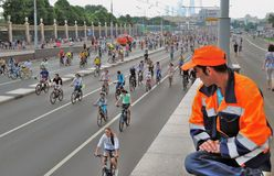 Road worker looks at сyclists riding on the road for cars Stock Photos
