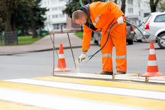 Road worker marking street lines zebra crossing. Road painter man worker marking street lines zebra crossing traffic sign using paint sprayer gun Stock Photos