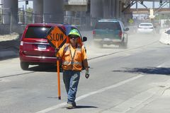 Road worker in an orange vest shows a road sign Slow. Milpitas, California, United States - July 29, 2016: American road worker in an orange vest shows a road Stock Photography