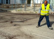 Road worker spraying bitumen emulsion. With the hand spray lance before applying a new layer of asphalt stock photography