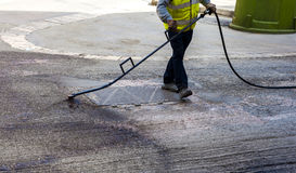 Road worker spraying bitumen emulsion. With the hand spray lance before applying a new layer of asphalt stock image