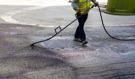 Road worker spraying bitumen emulsion Stock Image