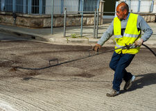 Road worker spraying bitumen emulsion Stock Photos