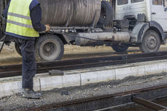 Road worker spraying manually bitumen emulsion. With the hand spray lance Royalty Free Stock Photos