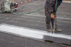 Road worker spraying pedestrian crosswalks 2. Road worker spraying pedestrian crosswalks with hand spraying equipment Royalty Free Stock Images