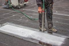 Road worker spraying pedestrian crosswalks. With hand spraying equipment Stock Image