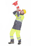 A road worker. Using a cone as a loudhailer Royalty Free Stock Images