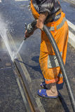Road worker wearing slippers and using water jet 2. Road worker wearing slippers and using water jet to remove detritus from tram tracks Stock Photo