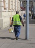 Road worker with yellow paint bucket Stock Image