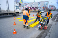 Road workers cause a marking of  pedestrian crossing . Road workers cause a marking of a pedestrian crossing . Langepas, Yugra Stock Photo