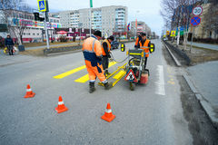 Road workers cause a marking of  pedestrian crossing . Road workers cause a marking of a pedestrian crossing . Langepas, Yugra Stock Image
