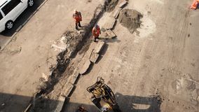 Road workers and excavator. Top view of two men. Renewal of pavement. Must finish work in time stock video