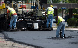 Road workers with hot asphalt Royalty Free Stock Image