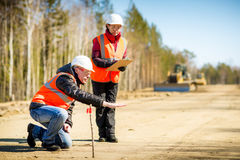 Road workers inspecting construction. Road engineer workers inspecting road reconstruction and processes Stock Photo