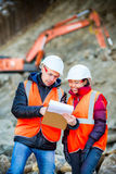 Road workers inspecting construction. Road engineer workers inspecting road reconstruction and processes Royalty Free Stock Image