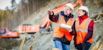 Road workers inspecting construction. Road engineer workers inspecting road reconstruction and processes Royalty Free Stock Photo
