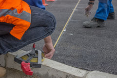 Road workers marking asphalt for painting Royalty Free Stock Image