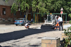 Road workers put asphalt on the road. Royalty Free Stock Photo