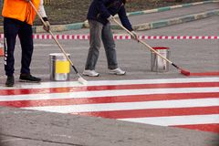 Road workers put a red and white strip of road markings on the asphalt royalty free stock photo