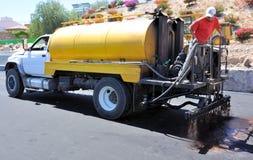Road works. Road under construction applying liquid asphaltic emulsion Royalty Free Stock Image