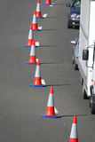 Road Works. A line of traffic cones reducing traffic to a single line. Short DOF, focus on 3rd cone, and some motion blur on rear vehicle Stock Image