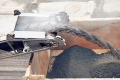 Road works. Asphalt removing machine loading powdered asphalt on the truck. Removed the old asphalt pours from the conveyor belt road milling machine stock images