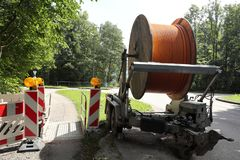 Road works with cable reel. Big cable drum near the street with broadband cable Stock Photo
