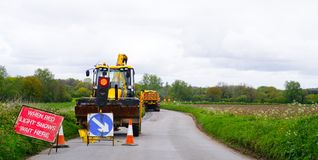 Road Works. With digger, lorry and traffic lights on a country lane in Norfolk uk royalty free stock images