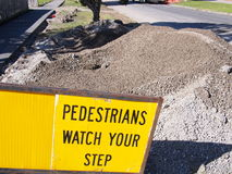 Road works gravel pile with a pedestrian warning sign Royalty Free Stock Photo