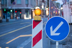 Road works. Safety lamp and signs announcing temporary road works in progress Royalty Free Stock Image