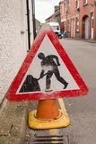 Road Works Sign. Battered road works sign in an urban terraced street in the United Kingdom stock images