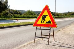 Road works sign for construction works in city street. Road under construction traffic sign. Traffic, warning sign road repairing. Outdoor street sign. Red Royalty Free Stock Photo