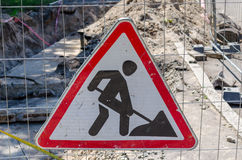 Road works sign hanging on a fence. Royalty Free Stock Photos