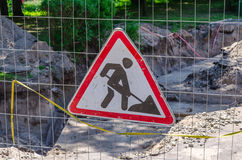 Road works sign hanging on a fence. Stock Image