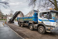 Road works in UK. LONDON, UK - CIRCA 2013: Highway contractors resurface the tarmac of a suburban road in London, UK Stock Images