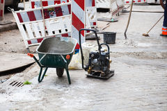 Road works. With a wheelbarrow and a plate compactor Royalty Free Stock Photos