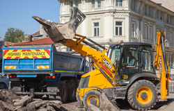 Road works. Yellow tractor removes old asphalt Stock Photo