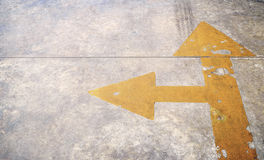 A road with yellow arrow on concrete background Stock Photos