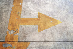 A road with yellow arrow on concrete background Stock Image