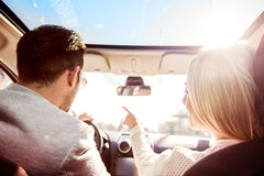 On the road. A young women and a young men are laughing in the car, enjoying in the road trip. The men is driving Royalty Free Stock Images