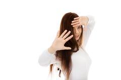 Roade skinn för ung kvinna bak hennes händer arkivfoton