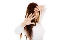Roade skinn för ung kvinna bak hennes händer royaltyfria bilder