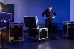 Roadie standing next to an unpacked flightcase Stock Photos