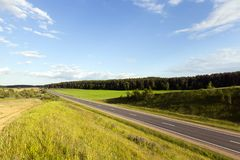 Roads with green grass. Asphalt road along which grows green grass and trees. Landscape with blue sky in the summer. Picture from a hill Stock Photo