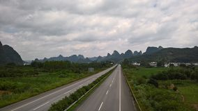 The roads and the mountains in the distance. The straight road leads to the mountains and there are some villages on the roadside stock image