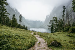 Roads to a beautiful lake which was surrounded by mountains and trees. Stock Images