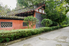 Roadside aged Chinese building with enclosure in trees and shrub Royalty Free Stock Images