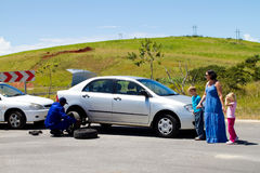 Roadside assistance. Automobile technician helping a mother and kids changing flat tyre on side of road