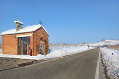 Roadside chapel and snowy vineyards. Piedmont, Italy. Royalty Free Stock Photo